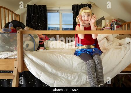 Ritratto di giovane ragazza seduta sul letto, indossando abiti fantasiosi costumi Foto Stock
