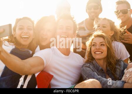 Gruppo di amici prendendo selfie sulla spiaggia Foto Stock