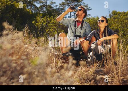 Colpo all'aperto di coppia giovane seduti insieme prendendo una pausa sulla passeggiata. Uomo caucasico e donna Foto Stock