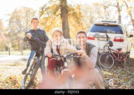 Ritratto padre e figli con le biciclette in autunno park Foto Stock