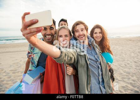 Gruppo di amici sulla spiaggia, tenendo autoritratto con lo smartphone Foto Stock