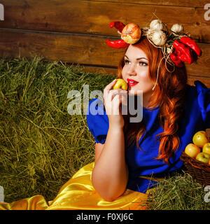 Una giovane ragazza detiene una mela matura vicino a cestello con un raccolto di frutta e verdura. Harvest Festival. Foto Stock