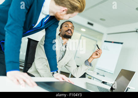 Un nero giovane con dreadlocks e un giovane bello dai capelli rossi imprenditore a discutere di grafica difetti Foto Stock