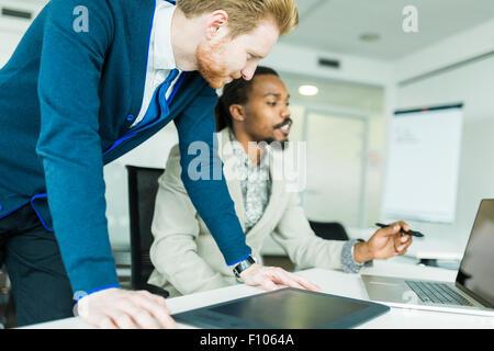 Un nero giovane con dreadlocks e un giovane bello dai capelli rossi imprenditore per discutere la progettazione Foto Stock