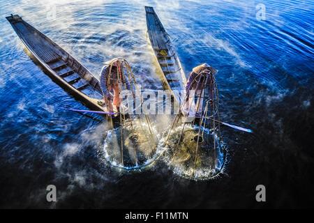 Angolo di alta vista di pescatori asiatici tramite rete da pesca in canoa sul fiume Foto Stock