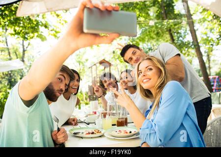 Ritratto di un allegro amici facendo selfie foto sullo smartphone in un ristorante esterno Foto Stock