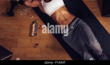 Vista superiore della giovane donna con abs muscolare sdraiato sul materassino yoga in palestra. Ritagliato colpo Foto Stock