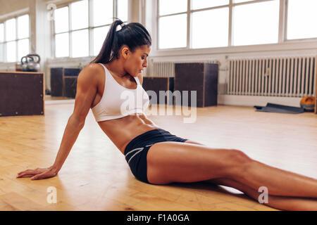 Ritratto di muscolare di giovane donna rilassante dopo allenamento in palestra. Montare atleta femminile prendendo Foto Stock