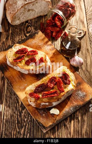 Bruschetta con pomodori secchi, aglio e olio di oliva. La cucina tradizionale italiana sandwich made di grigliate Foto Stock