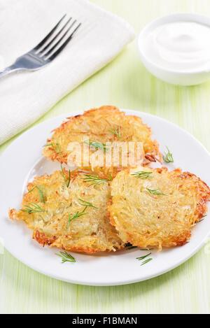 Frittelle di patate con aneto su piastra bianca Foto Stock