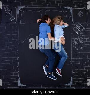 Coppia giovane dormire nel letto, tenendo le mani, l'uomo è di abbracciare la sua donna. Giovani papà dormire con Foto Stock