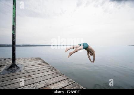 Uomo maturo saltando in acqua sul molo, Baden-Württemberg, Baviera, Germania Foto Stock