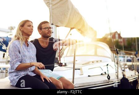 Dolce giovani innamorati seduti di fronte a uno yacht e guardando in lontananza durante il tramonto. Foto Stock
