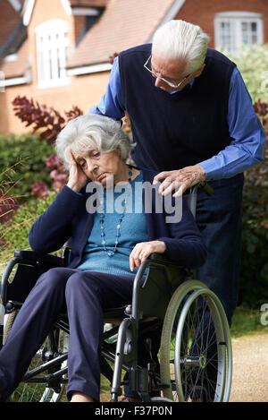 Premuto Senior donna in carrozzella essendo spinto dal marito Foto Stock