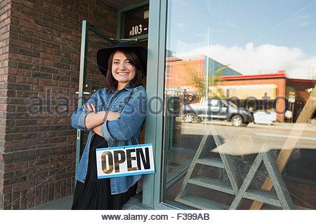 Ritratto fiducioso titolare di azienda con open firmare storefront Foto Stock