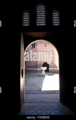 Il cortile delle Sette Chiese - Sette Chiese - di Piazza Santo Stefano visto attraverso una porta aperta Bologna Foto Stock