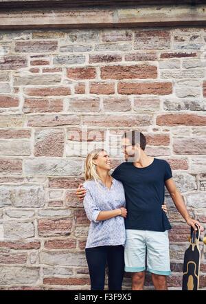 Tre quarti di colpo di una felice coppia dolce con lo skateboard, sorridente ad ogni altra contro la parete in calcestruzzo Foto Stock