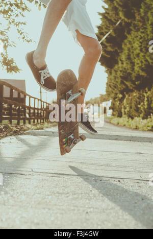 Giovane uomo skateboarding in estate Foto Stock