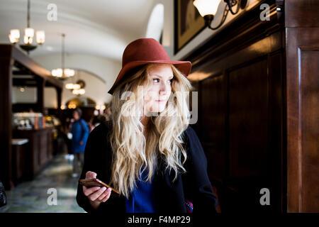 Riflessivo freelancer azienda smart phone mentre in piedi presso il cafe Foto Stock