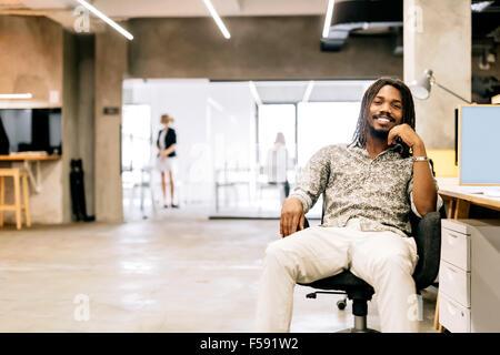 Bello graphics designer seduti ad una scrivania in un ufficio Foto Stock
