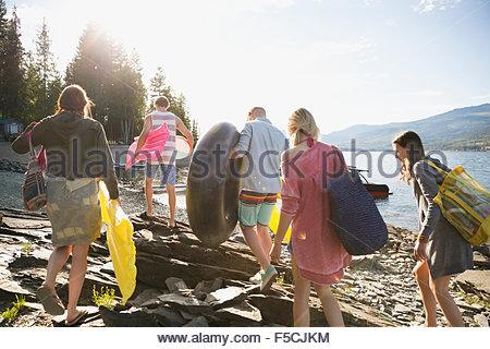 Giovani amici trasportare zattere in piscina a sunny lakeside Foto Stock