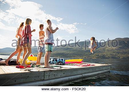 Giovani amici guardare la donna salta fuori il lago di dock Foto Stock