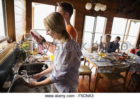 Giovane lavaggio piatti nella cucina di cabina Foto Stock