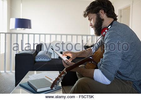 Uomo con registrazione di chitarra con musica digitale compressa Foto Stock