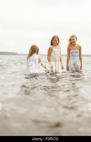 La Svezia, Vastmanland, Bergslagen, Hallefors, Sangshyttan, tre ragazze (4-5, 8-9, 10-11) in piedi in acqua Foto Stock