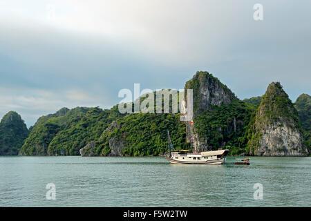 Giunche Cinesi al di ancoraggio e calcare (Carso tumuli, la baia di Ha Long, Bai Tu Long Settore, vicino a Ha Long, Foto Stock
