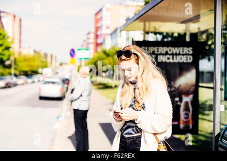 Considerato giovane donna usando il telefono mentre è in attesa vicino alla fermata del bus al marciapiede Foto Stock