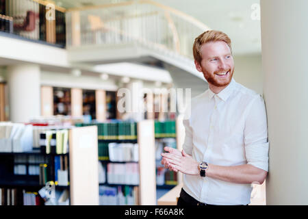 Bello intelligente studente maschio sorridente in biblioteca Foto Stock