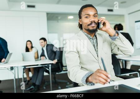 Nero bello graphics designer con dreadlocks mediante digitalizzatore in una ben illuminata, ordinato ufficio ambiente Foto Stock