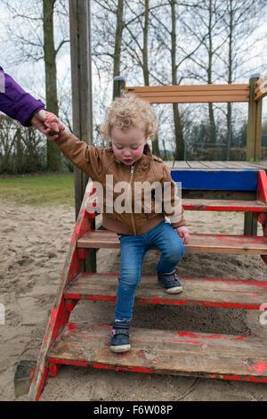 Madre aiutare piccola figlia percorrendo a piedi il parco giochi scale Foto Stock