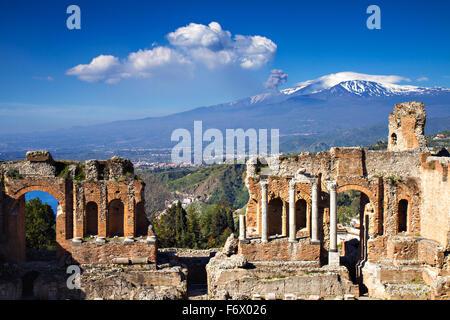 Le rovine del Teatro Greco Romano con eruzione dell'Etna, Taormina, Sicilia, Italia Foto Stock