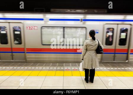 Una donna giapponese in attesa in metropolitana per il passaggio di un treno Foto Stock