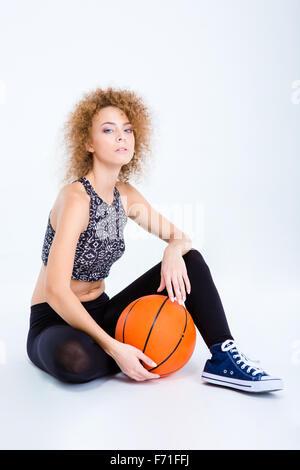 Ritratto di una giovane donna sportiva seduto sul pavimento con basket ball isolata su uno sfondo bianco Foto Stock