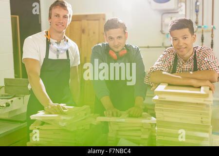 Ritratto fiducioso carpentieri con cataste di legno in officina Foto Stock