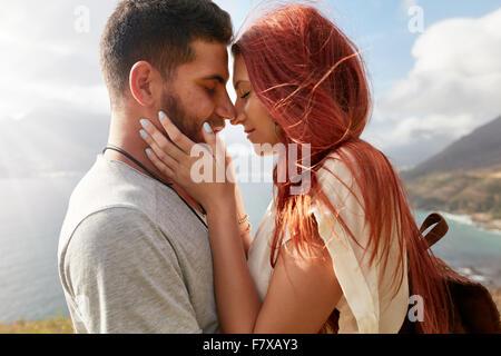 Ritratto di affettuosa coppia giovane circa a kiss. Romantico giovane uomo e donna la condivisione di un bel momento Foto Stock
