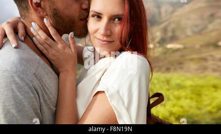 Immagine ravvicinata di attraente giovane donna che abbraccia il suo ragazzo all'esterno. Romantica una giovane Foto Stock