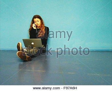 Giovane donna parlando al telefono mentre è seduto sul pavimento con il computer portatile Foto Stock