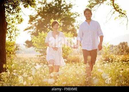 Felice e giovane coppia incinta abbracciando nella natura Foto Stock