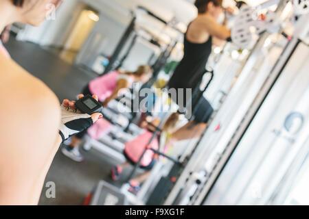 Donna prendendo il tempo mentre atleta facendo pull-up in palestra Foto Stock