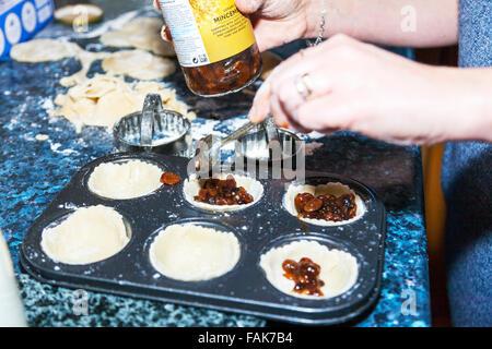 Fare pasticci di carne macinata aggiunta di macinato per casi di pasticceria cucina cucina nel vassoio da forno Foto Stock
