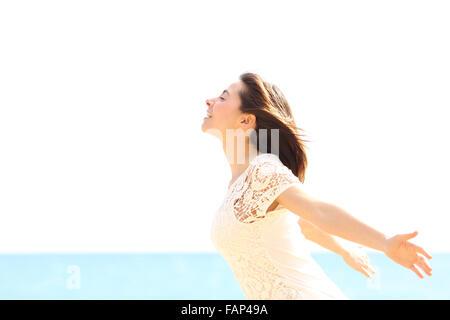 Donna felice godendo il vento e di respirare aria fresca sulla spiaggia in una posizione soleggiata e giornata di Foto Stock