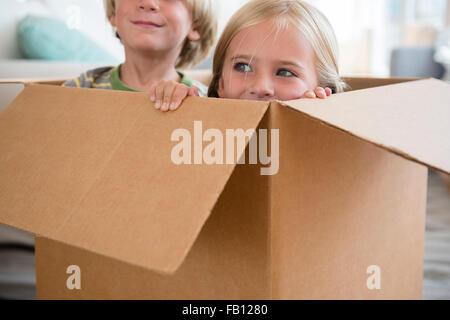 Ragazzo (4-5) e la ragazza (6-7) seduta nella casella Foto Stock