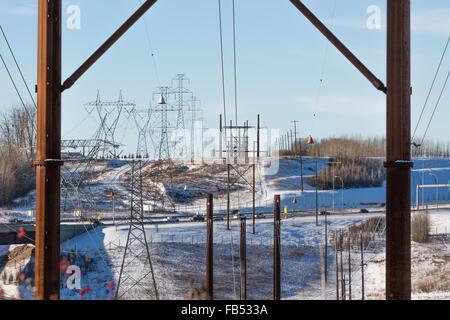 Le linee elettriche in alta tensione su entrambi i lati dell'autostrada Foto Stock