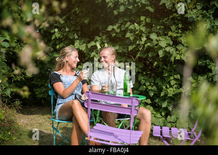 La Svezia, Skane, Osterlen, Rorum, giovane seduto al tavolo da giardino Foto Stock