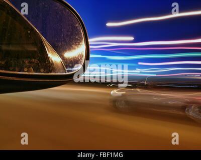 Specchio Side-View e sentieri di luce sulla strada di notte Foto Stock