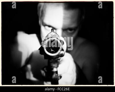 Uomo che ha di mira la pistola in telecamera Foto Stock